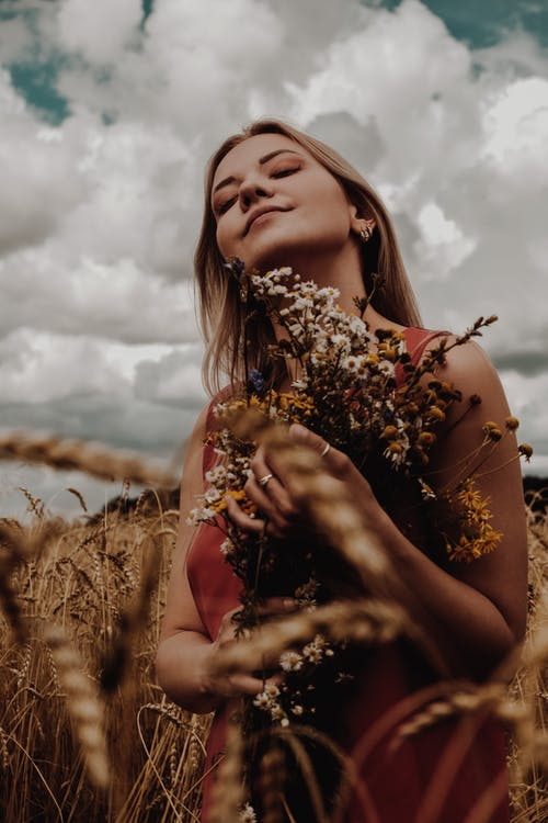 Young woman standing in dried field