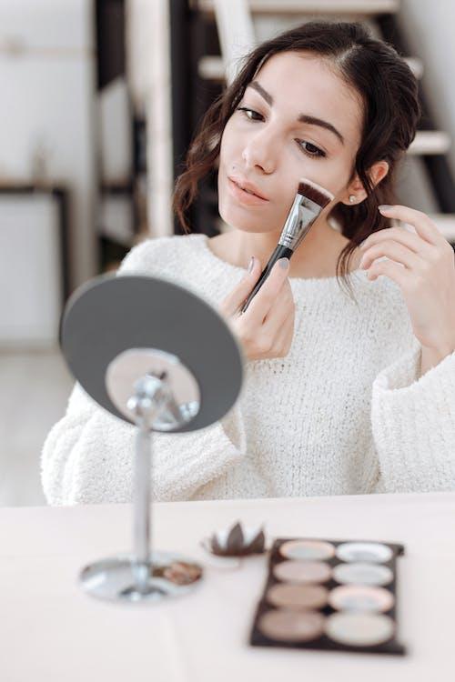 銀と黒の丸い鏡を保持している白いセーターの女性