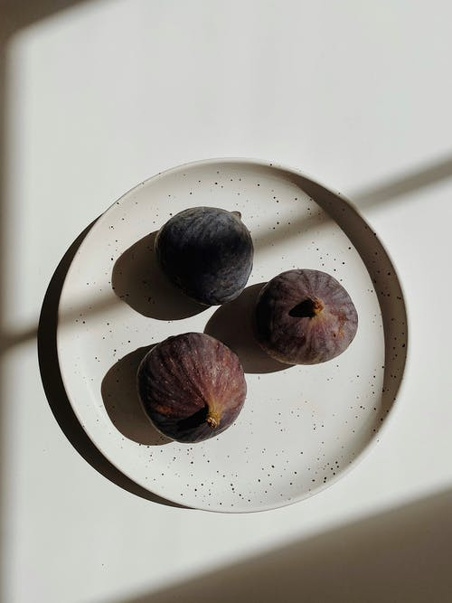 Fresh fig on plate in shadows