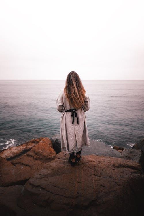 Woman standing on rocky shore near water