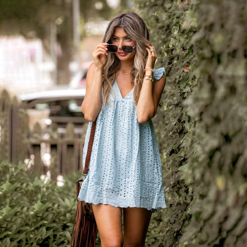 Trendy young female in stylish mini dress near bushes with verdant fresh leaves on blurred background