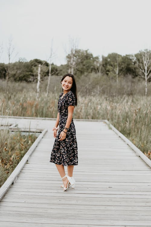 Smiling woman in dress on wooden path