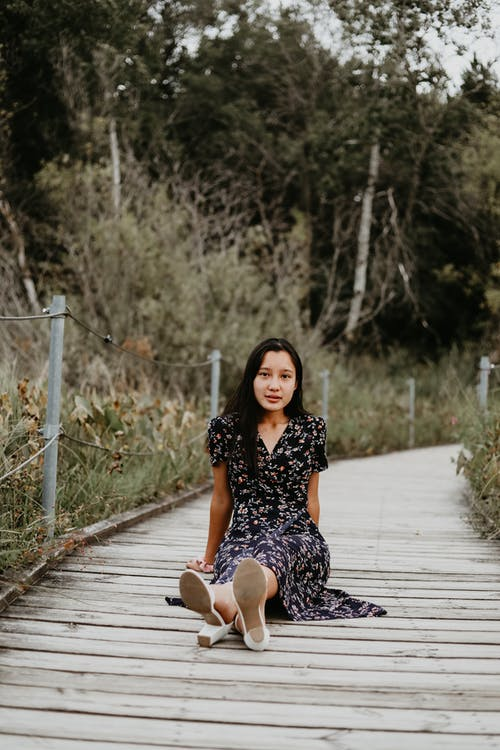 Asian woman sitting on wooden footpath