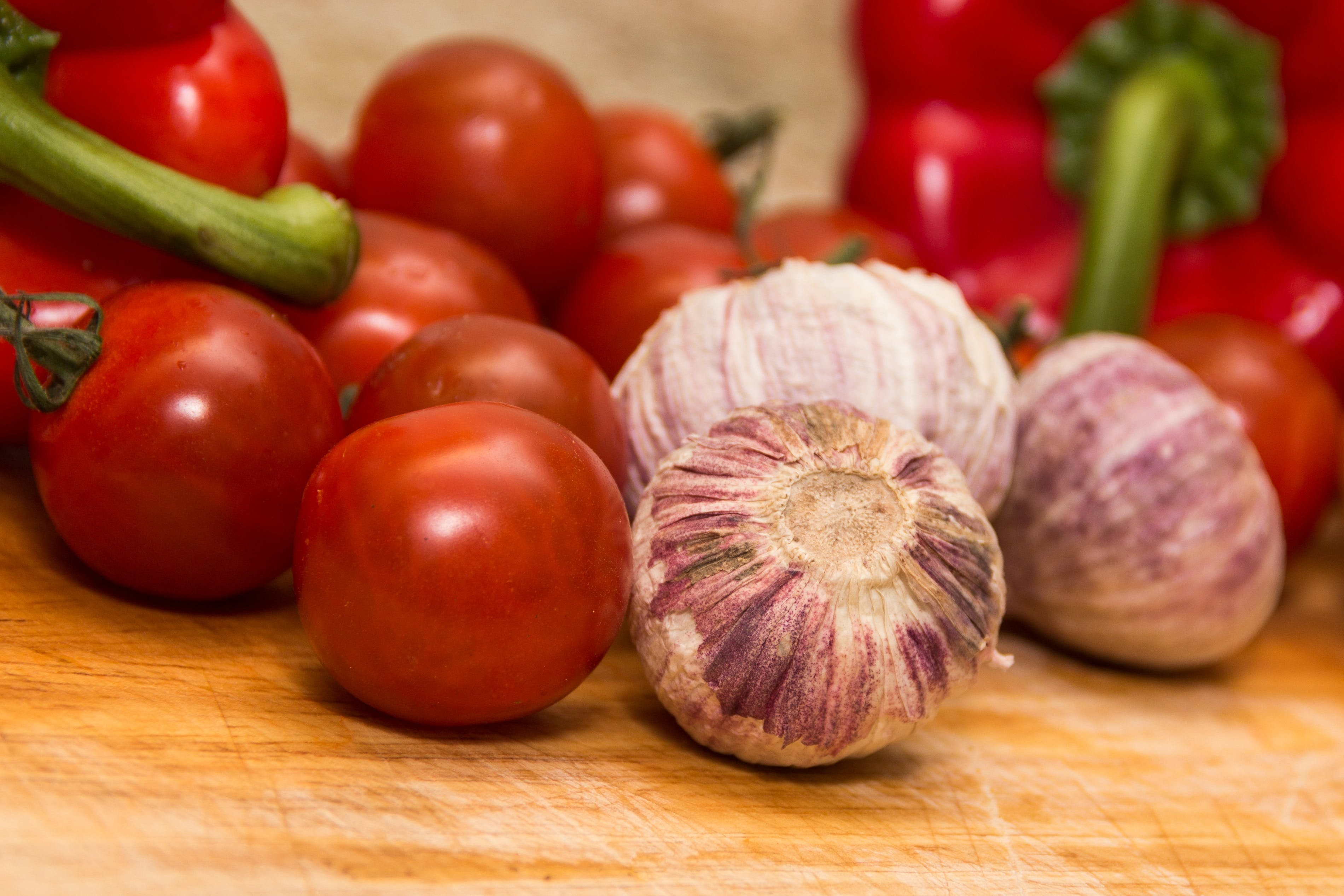 Red Tomatoes Beside Red Onions on Brown Wooden Table