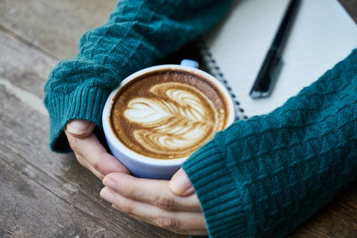Person Touching Mug With Latte Art