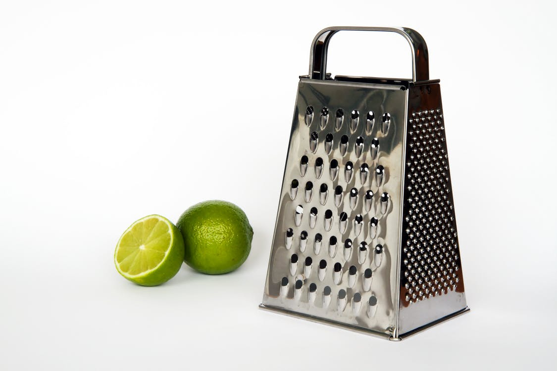 Gray Cheese Grater on White Surface Beside Two Lemons