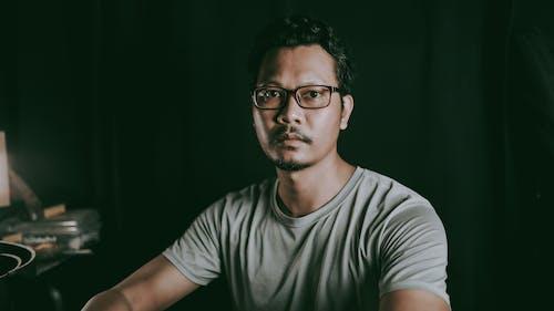 Serious Asian man sitting in dark room