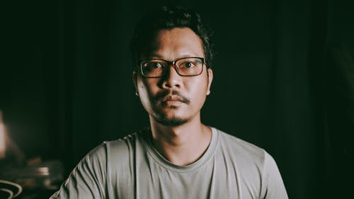 Emotionless bearded Asian male in casual shirt and eyeglasses sitting in dark room and looking away