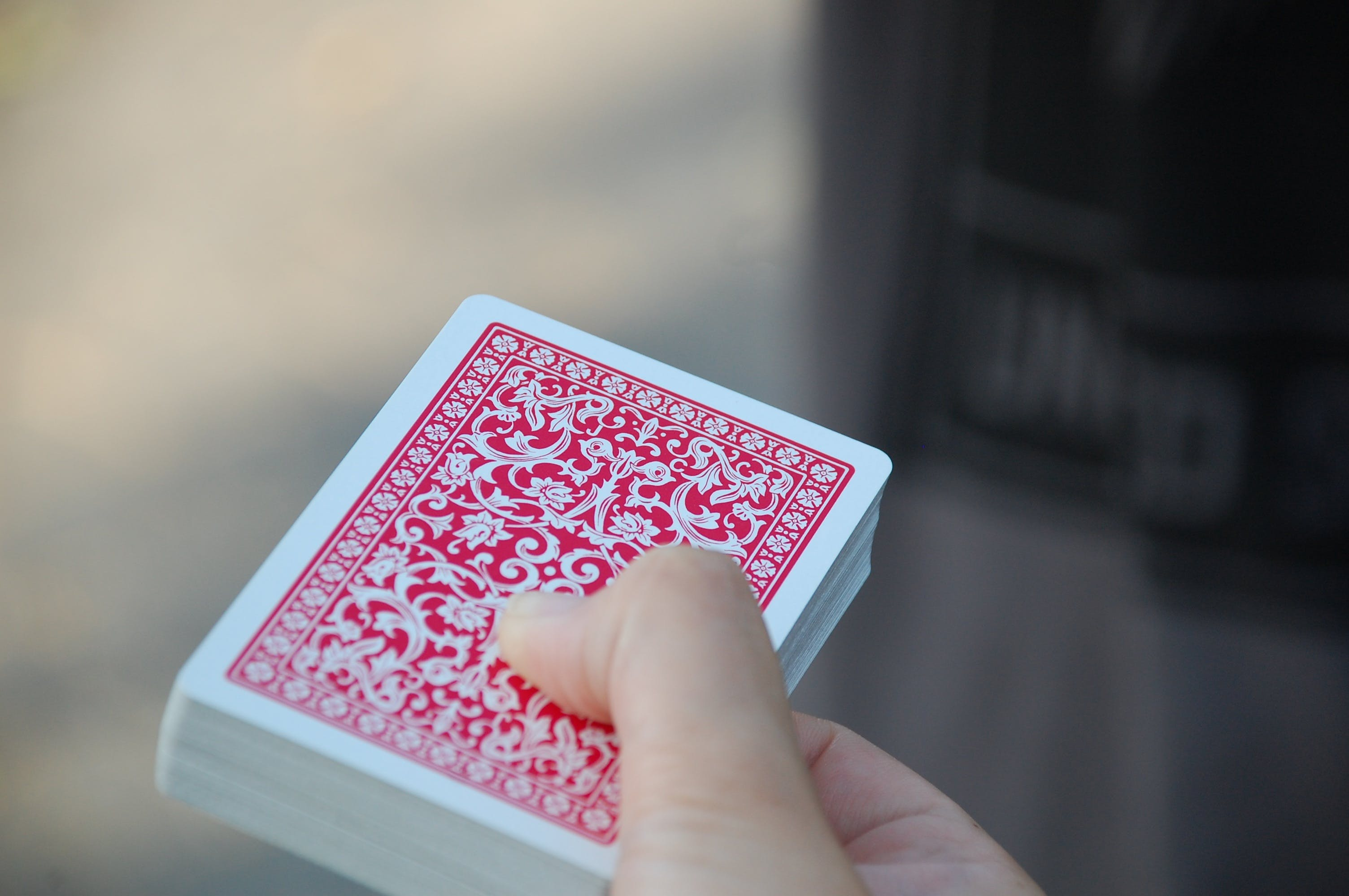 Person Holding Red-and-white Floral Playing Cards