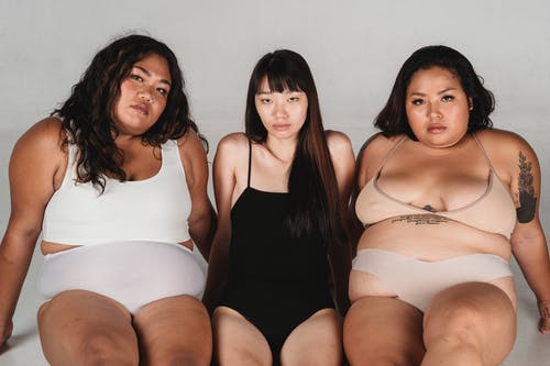 Calm Asian skinny woman wearing black bodysuit sitting on floor between plus size female models in light underwear against white wall and looking at camera