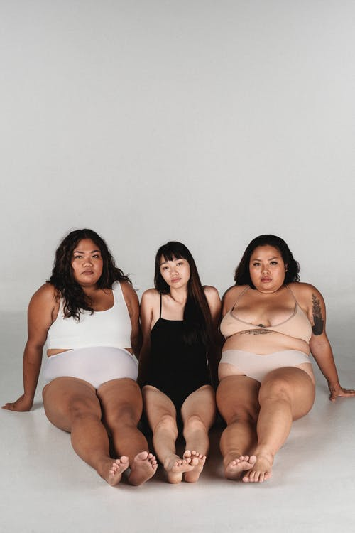 Calm Asian women in underwear sitting on floor in studio