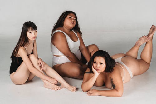 Full body emotionless Asian females with slim and overweight body complexions in lingerie resting on floor against white background during photo session in studio