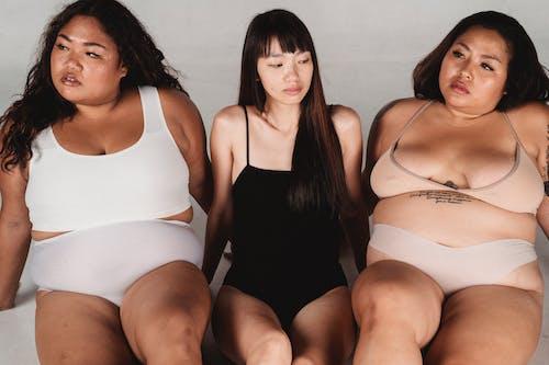 Serene Asian women in underwear sitting on floor