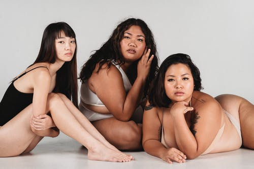Feminine Asian females with fit and overweight body complexions wearing lingerie and sitting together on floor against white wall in light studio