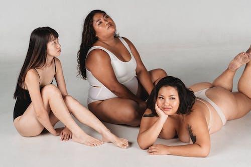 Dreamy Asian women in underwear resting on floor in studio