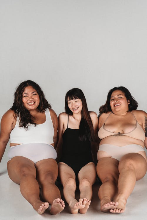 Smiling Asian females with different body complexions wearing lingerie sitting on floor and leaning on hands during photo session in light studio