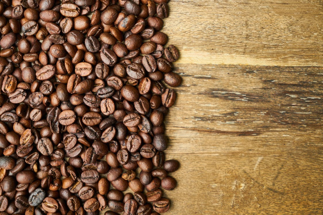 Coffee beans on wooden surface background