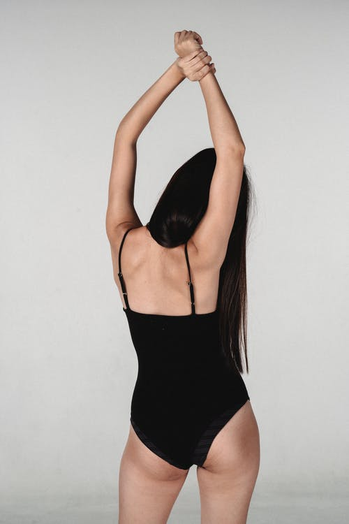 Back view of faceless female in black lingerie standing in studio with raised arms