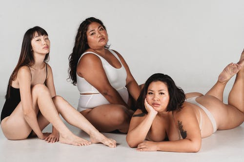 Calm Asian models with different complexion on floor in studio
