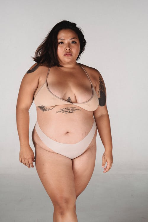 Plus size Asian female with tattoos on body and dark hair wearing lingerie looking at camera while standing on white background with crossed legs