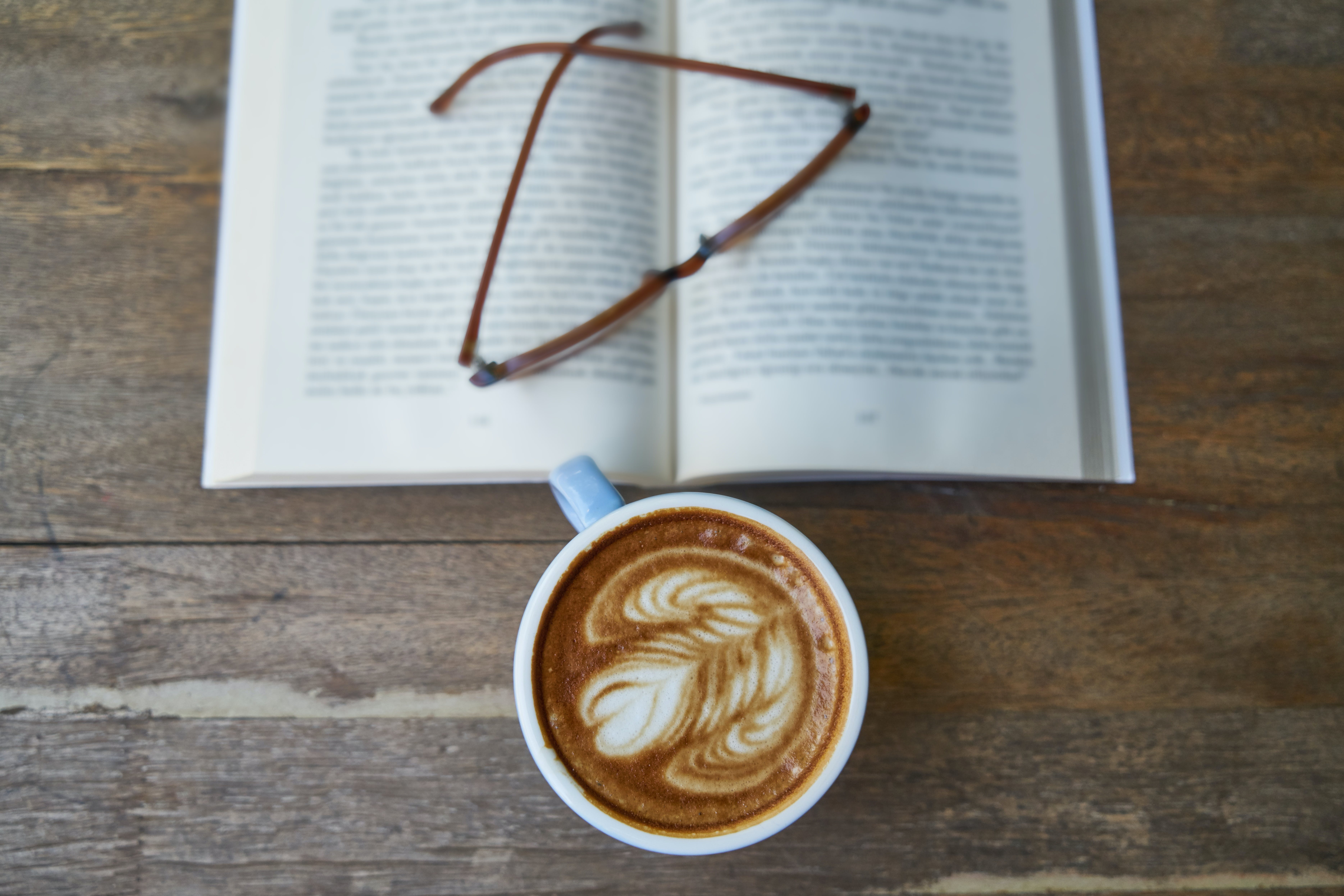 White Ceramic Mug Beside Eyeglasses Under the Book