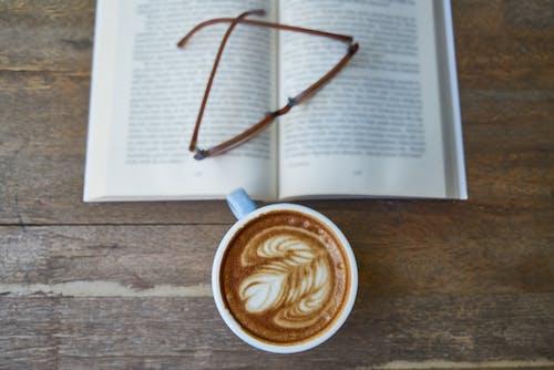 Белая керамическая кружка рядом с очками под книгой