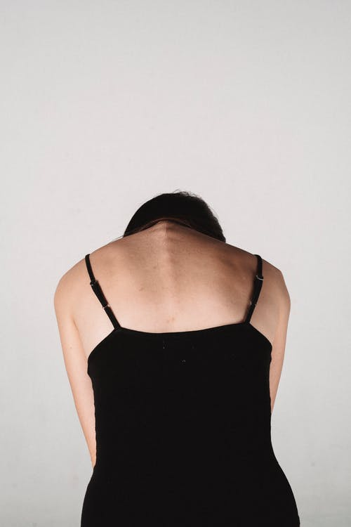Back view of anonymous female in black underwear sitting in floor against white background