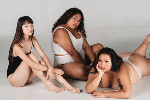 Sensual female models in underwear relaxing on floor while looking at camera against white background