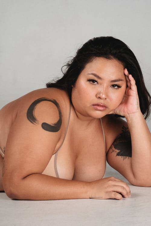 Confident Asian alluring young plus size woman leaning on hand while lying on floor in studio and looking at camera