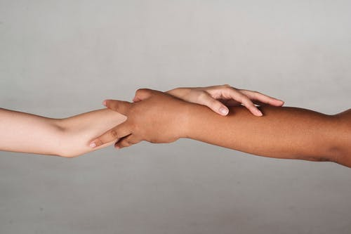 Crop anonymous multiracial female demonstrating unity and tolerance while reaching hands to each other in studio against gray background