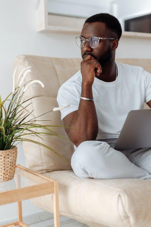 Мужчина в белой футболке с круглым вырезом сидит на белом диване