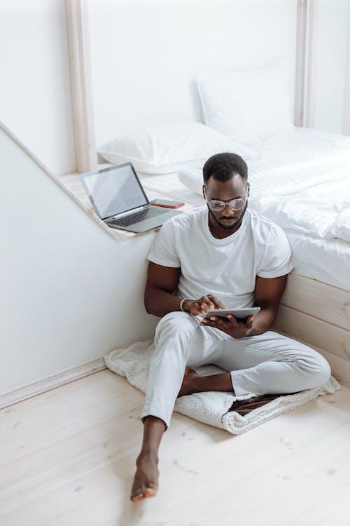 흰색 크루 넥 티셔츠와 침대에 앉아 흰색 바지에 남자