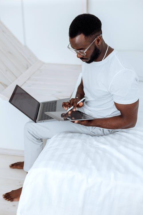 Người đàn ông Mặc áo Phông Trắng Cổ Thuyền Và Quần Trắng Ngồi Trên Giường Sử Dụng Macbook Bạc