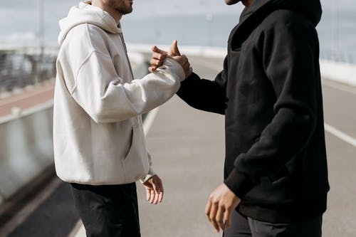 Man in White Hoodie and Black Pants Holding Hands With Man in Black Jacket
