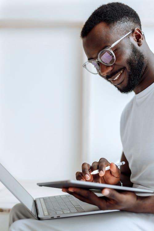 실버 Ipad를 들고 흰색 크루 넥 티셔츠에 남자