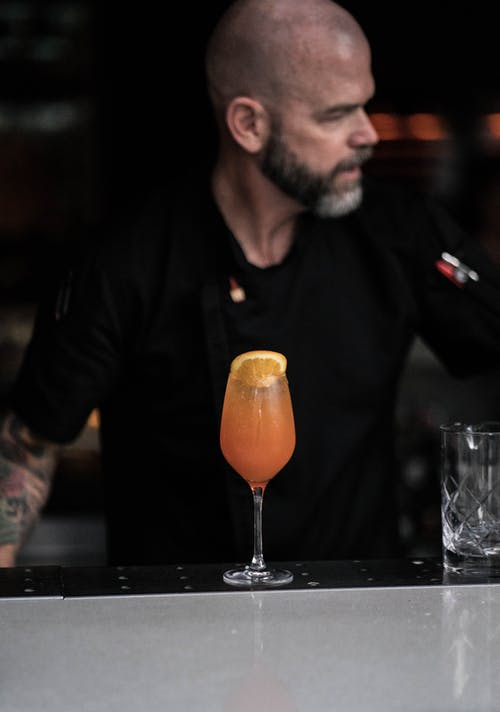 Trendy adult male bartender standing at counter with exotic cocktail