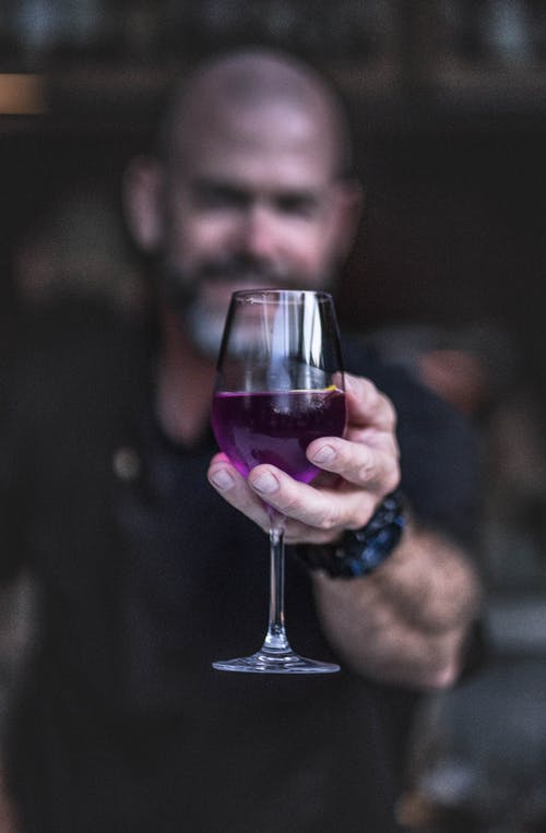 Cheerful bearded bartender in black shirt offering glass of purple alcohol drink in bar