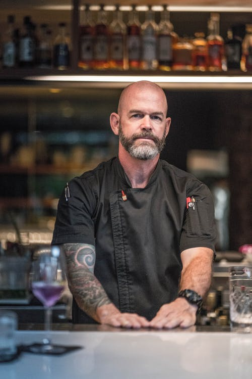 Serious bearded male bartender with tattoos on arm in uniform standing near bar counter and looking at camera