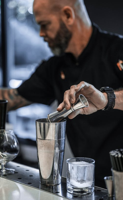 Crop focused bearded male barkeeper pouring ingredients into shaker while preparing cocktail at counter