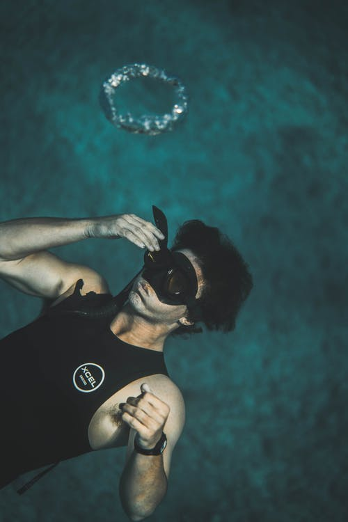 From above of anonymous young male in wetsuit and snorkeling mask submerging into water while preparing for diving