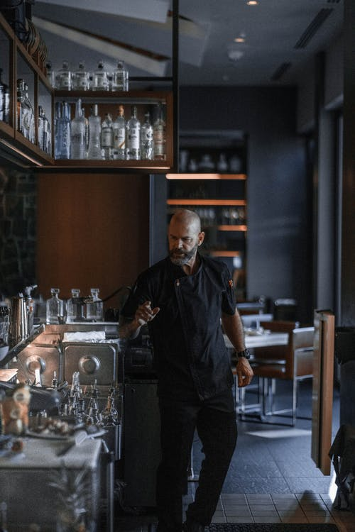Confident barman standing at bar counter with various bottles of alcohol drinks