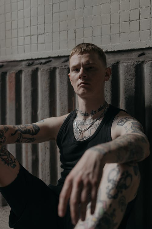 Man in Black Tank Top With Tattoo on His Right Arm