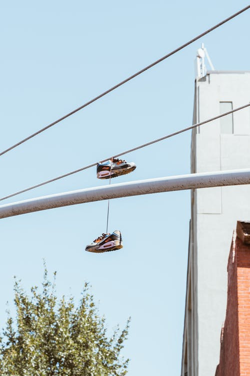 Sneakers hanging on metal chimney near wires