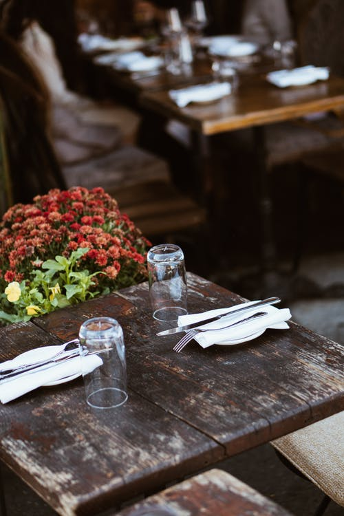 From above of served dishes with knives and forks with flowers on chair on blurred background of restaurant