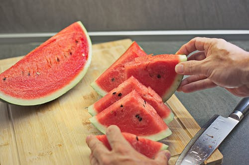From above crop anonymous person cutting fresh watermelon on wooden board while preparing fresh snack