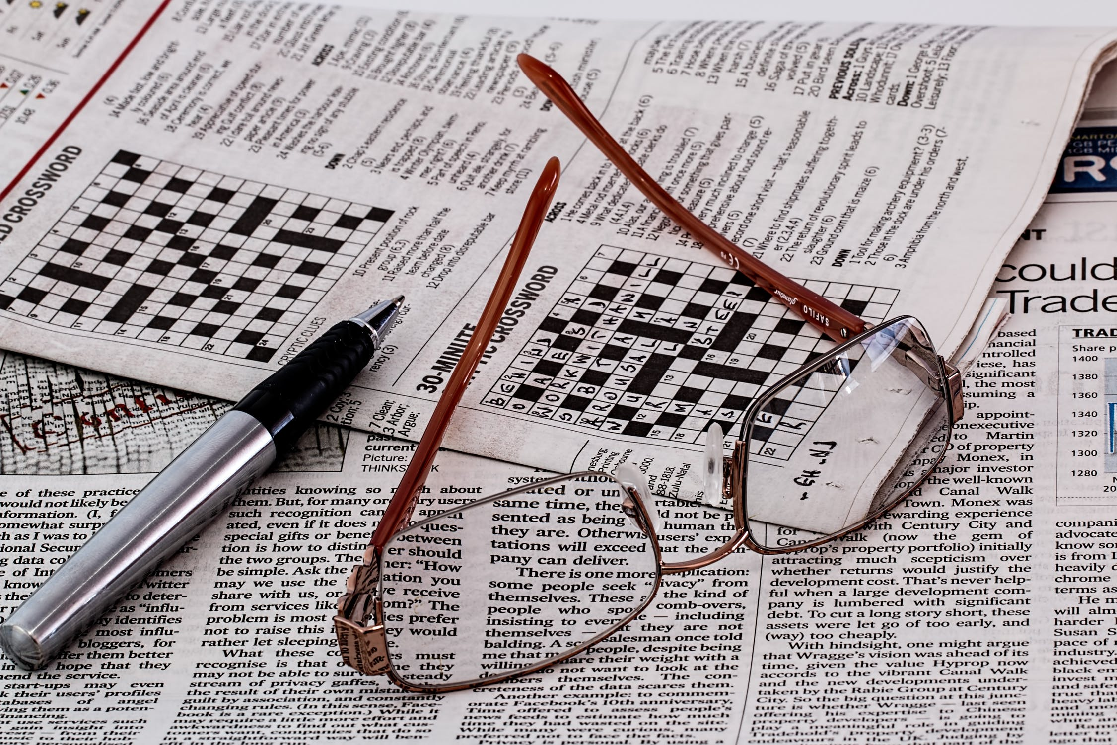Eyeglasses and pen on top of newspaper crossword