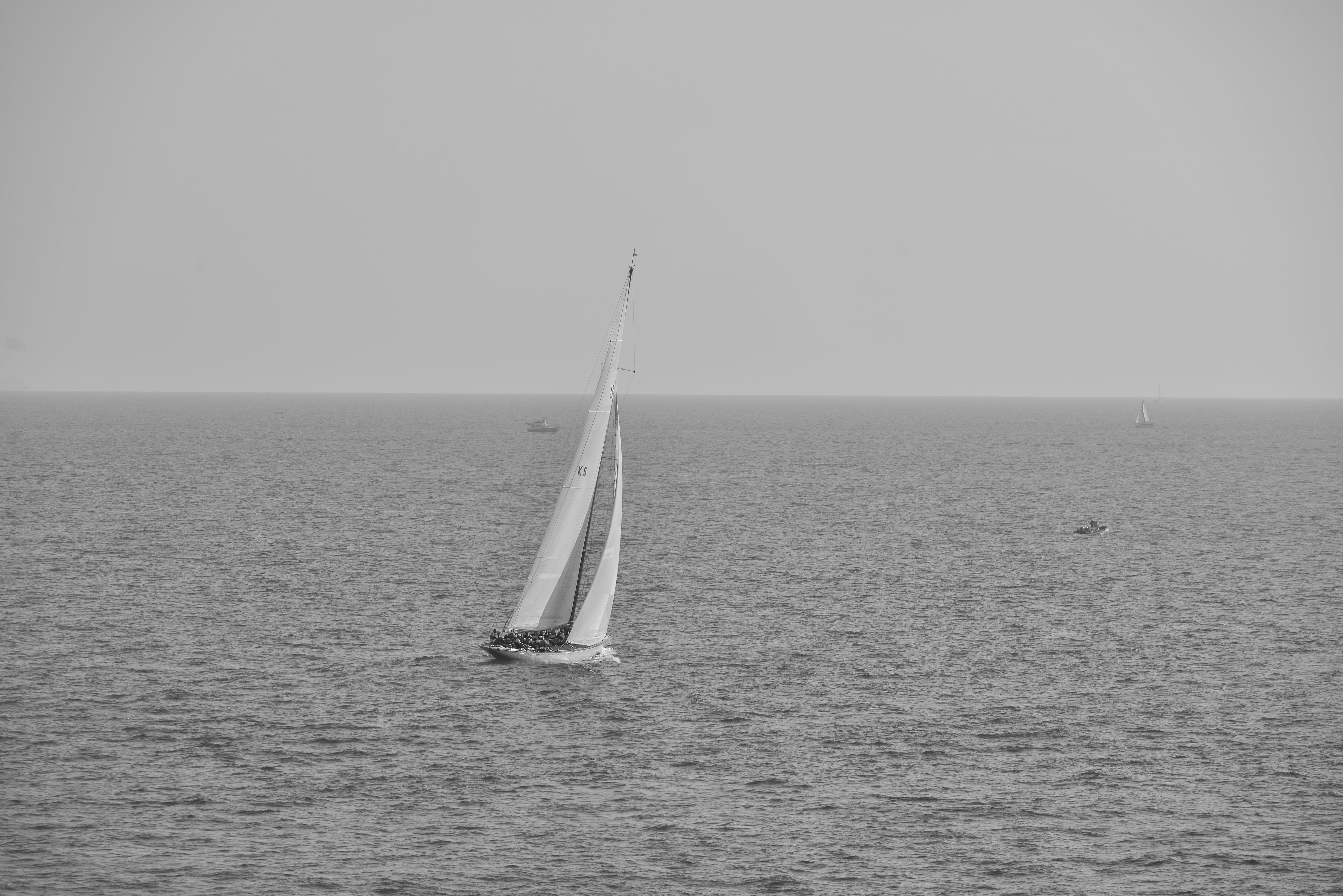 Grayscale Photography of Boat on Calm Body of Water