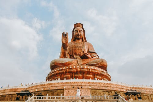 Statue of Buddha on old temple under sky