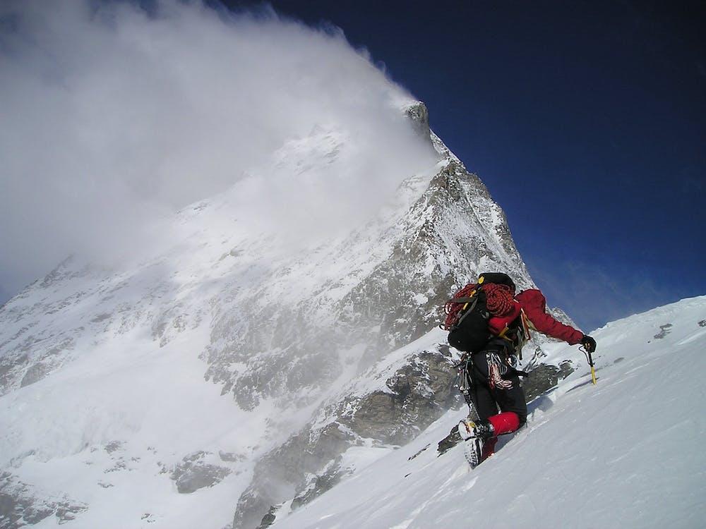 Person Climbing Glacier Mountain during Day