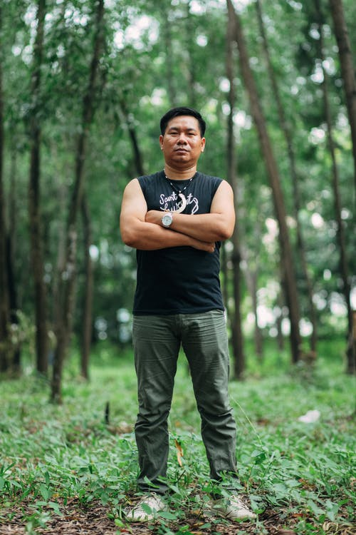 Low angle of young serious ethnic male in trendy wear standing with folded arms on grass meadow behind trees while looking at camera
